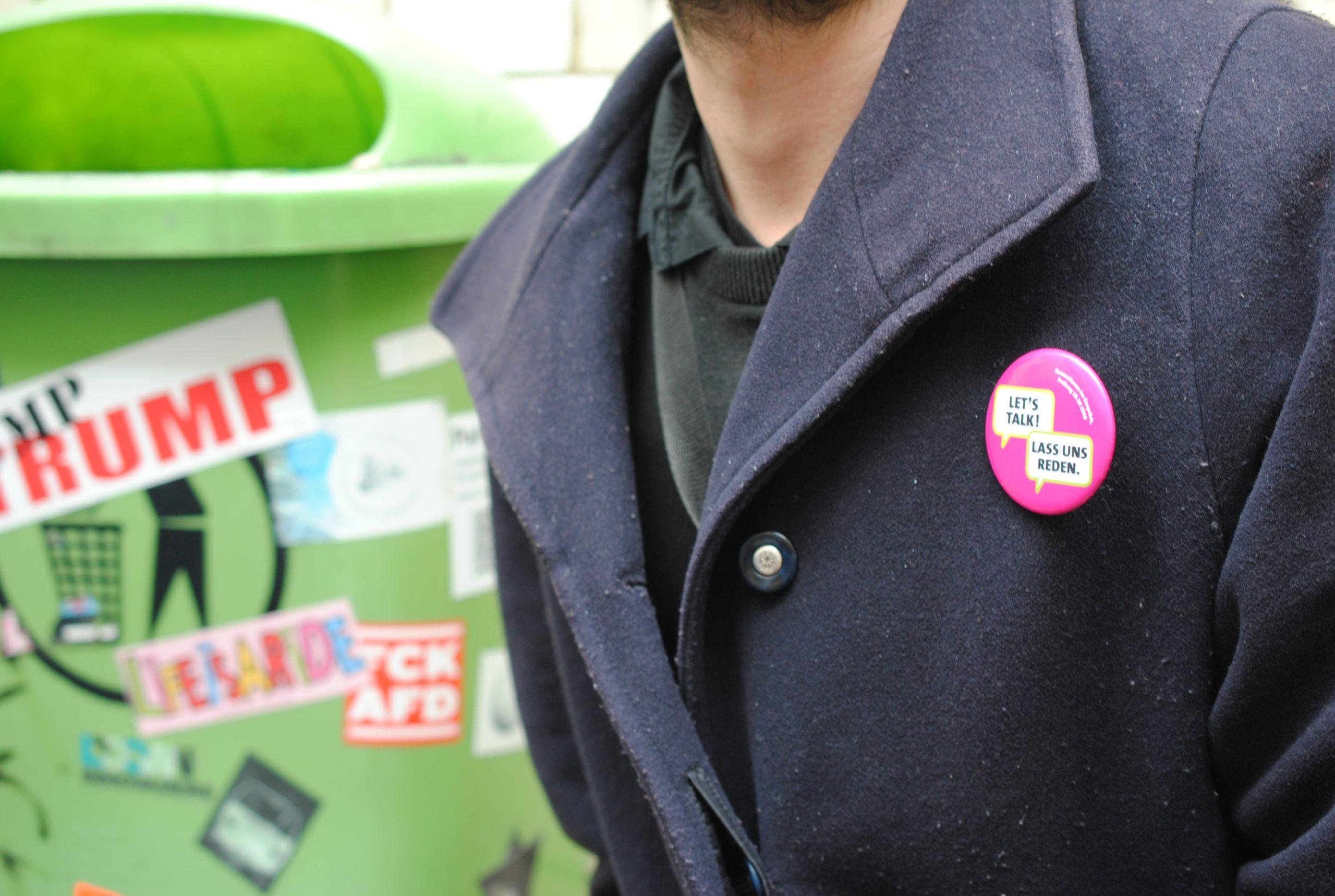 Der Pinkfarbene Button Ist Ein Resultat Von Generationen Im Gespräch In Freiburg. Der Button Ist Eine Aufforderung, In Der Öffentlichkeit Wieder Miteinander Ins Gespräch Zu Kommen.